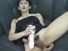 Asian shemale cums after didlofuck on leather sofa